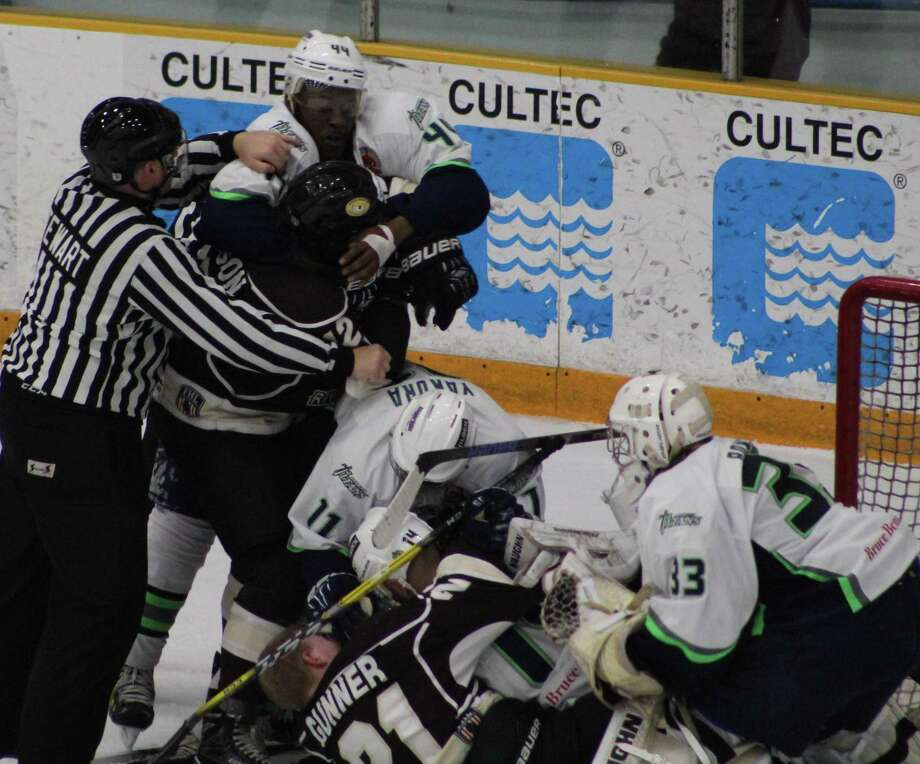 Lineman Mark Stewart, left, tries to separate the Danbury Titans' Steve Brown and the Berlin River Drivers' Patrick Harrison during a skirmish in front of Danbury Titans goalie Bobby Bowden (33) during Game 1 of the Federal Hockey League's Commissioner's Cup semifinals at the Danbury Arena April 7, 2017. Photo: Richard Gregory / Richard Gregory