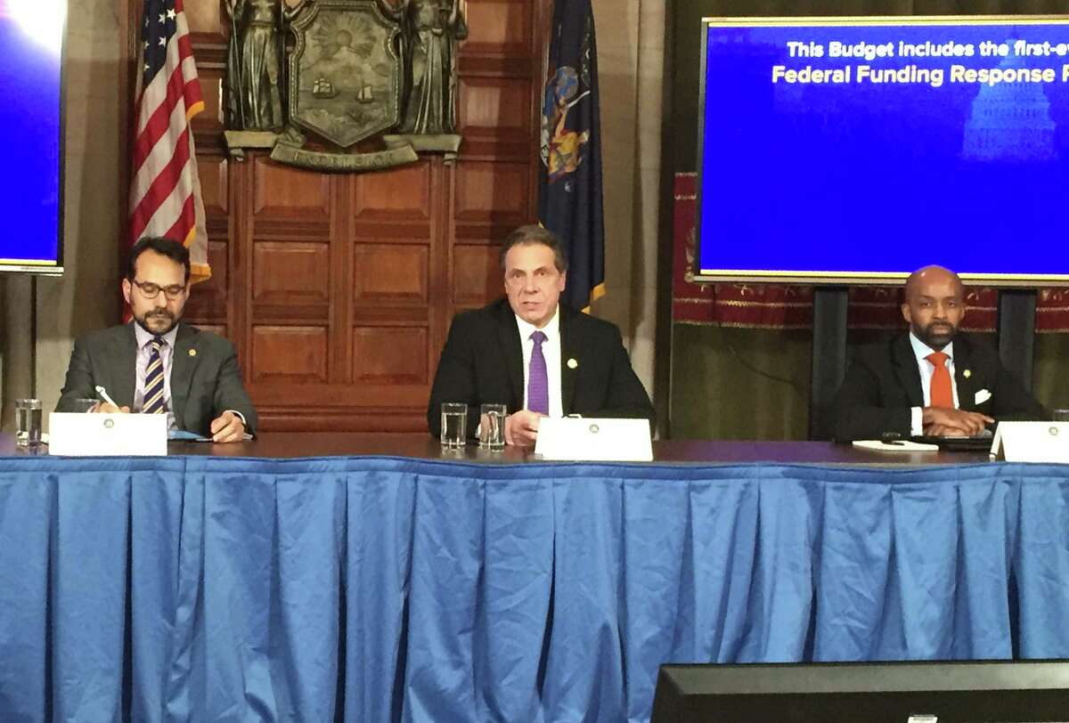 Gov. Andrew Cuomo is flanked by his Budget Director Robert Mujica, left, and Counsel Alphonso David as he briefs reporters on the major elements of the final state budget agreement on Friday evening at the state Capitol. (Casey Seiler / Times Union)
