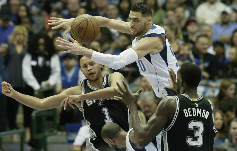 San Antonio Spurs guard Kyle Anderson (1) passes the ball past Dallas Mavericks center Salah Mejri (50) to Spurs center Dewayne Dedmon (3) during the first half of an NBA basketball game in Dallas, Friday, April 7, 2017. (AP Photo/LM Otero) Photo: LM Otero, STF / Associated Press / Copyright 2017 The Associated Press. All rights reserved.