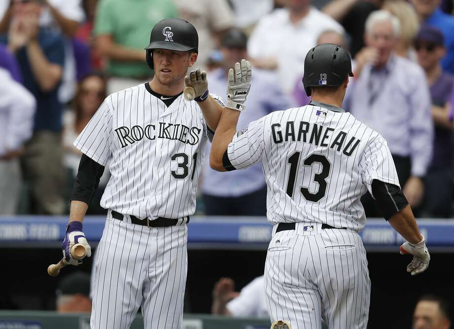 Colorado Rockies starting pitcher Kyle Freeland, left, congratulates Dustin Garneau as Garneau returns to the dugout after hitting a solo home run off Los Angeles Dodgers starting pitcher Hyun-Jin Ryu in the fifth inning of a baseball game Friday, April 7, 2017, in Denver. (AP Photo/David Zalubowski) Photo: David Zalubowski, Associated Press