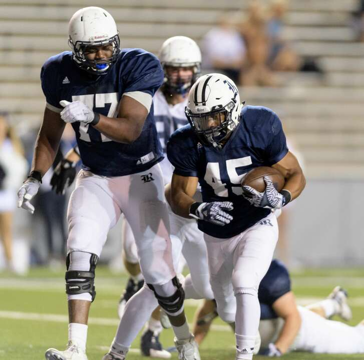 Samuel Stewart (45) of the Rice Owls runs behind Uzoma Osuji (77) for a touchdown in the second half of the Rice Owls Spring Football game on Friday, April 7, 2017 at Rice Stadium in Houston Texas.