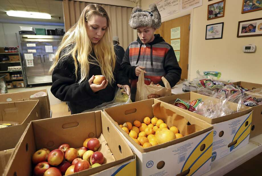 Sunny Larson (left) and Zak McCutcheon shop last month at the Augusta Food Bank in Maine. Republican Gov. Paul LePage says his call to ban the use of food stamps for soda and candy is backed by science and a desire to reduce obesity and diabetes. Photo: Robert F. Bukaty, Associated Press