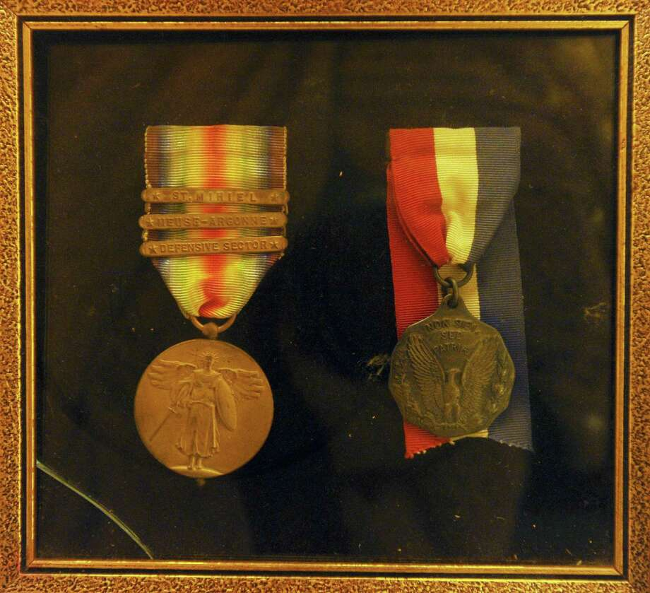 Medals awarded to local WWI participants, for the war campaign and nursing services, sit under glass inside the Stamford Historical Society. Photo: Michael Cummo / Hearst Connecticut Media / Stamford Advocate