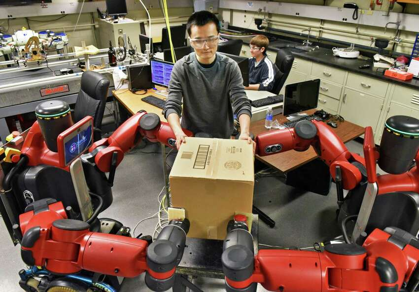 Student Yuan-Chih Peng works coordinates a pair of Baxter on wheels industrial robots to work together under human guidance at RPI's CATS robotics lab Thursday April 6, 2017 in Troy, NY. (John Carl D'Annibale / Times Union)