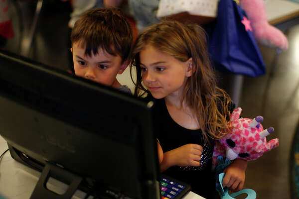 John Dach, age 4, and Mary Dach, age 6, play games after the stuffed animal sleepover April 8, 2017, at the Midland County Public Library Centennial Branch. Kids dropped off their stuffed animals the night before and returned in the morning to discover what the animals did during the night.  James Durbin/Reporter-Telegram