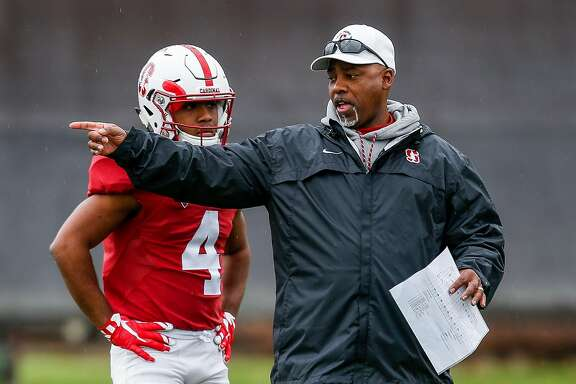 Stanford running back coach Ron Gould talks with wide receiver Jay Tyler (4) during spring football practice on Saturday, April 8, 2017 in Stanford, Calif.