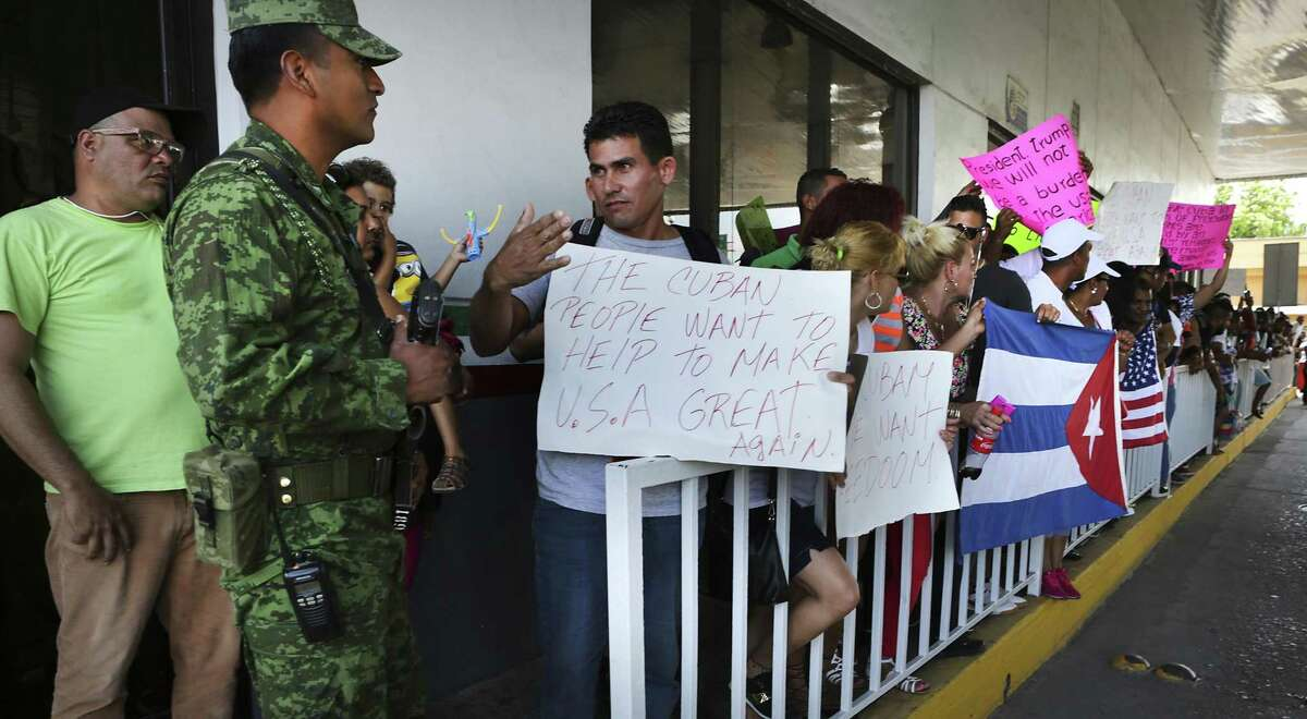 Cuban immigrant Reinier Aguila Esquivel talks with a Mexican soldier as he and other Cubans stranded in Nuevo Laredo, Mexico attempt to pass to the international bridge following a rally and march from Plaza Juarez to the International Bridge, on Saturday, April. 8, 2017.