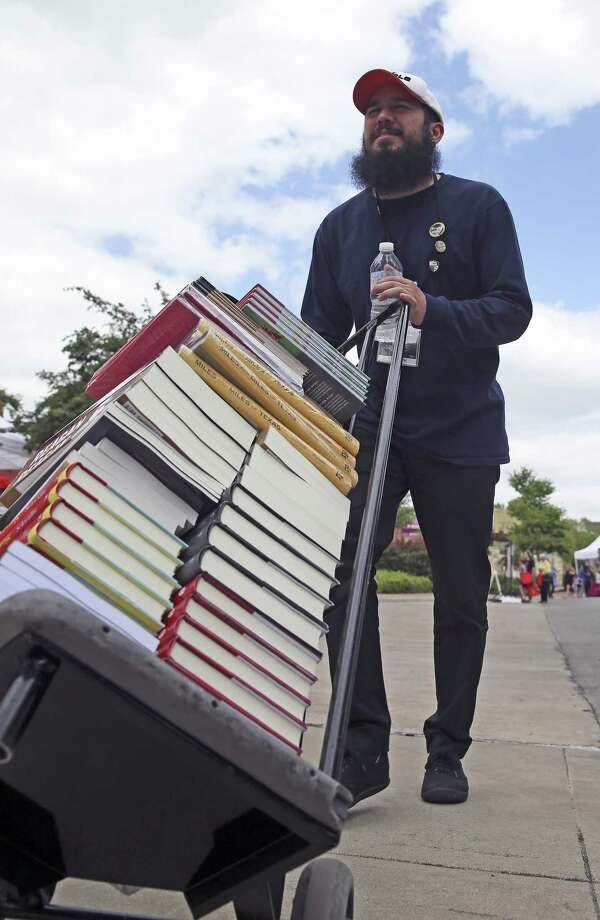 Mathew Hernandez wheels more Barnes and Noble books out for sale as the Fifth Annual San Antonio Book Festival attracts crowds at the Central Library on April 8, 2017. Photo: Tom Reel, Staff / San Antonio Express-News / 2017 SAN ANTONIO EXPRESS-NEWS