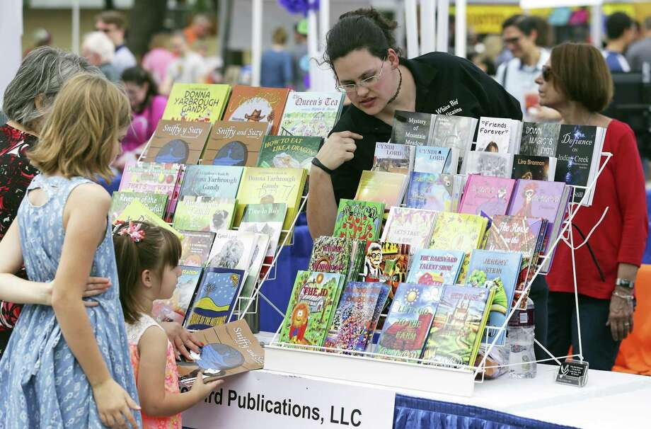 White Bird Publications author Beth Lauzier leans out to help customers during the 2017 San Antonio Book Festival. This year's edition, the sixth annual, is scheduled for April 7. Photo: Tom Reel /San Antonio Express-News / 2017 SAN ANTONIO EXPRESS-NEWS