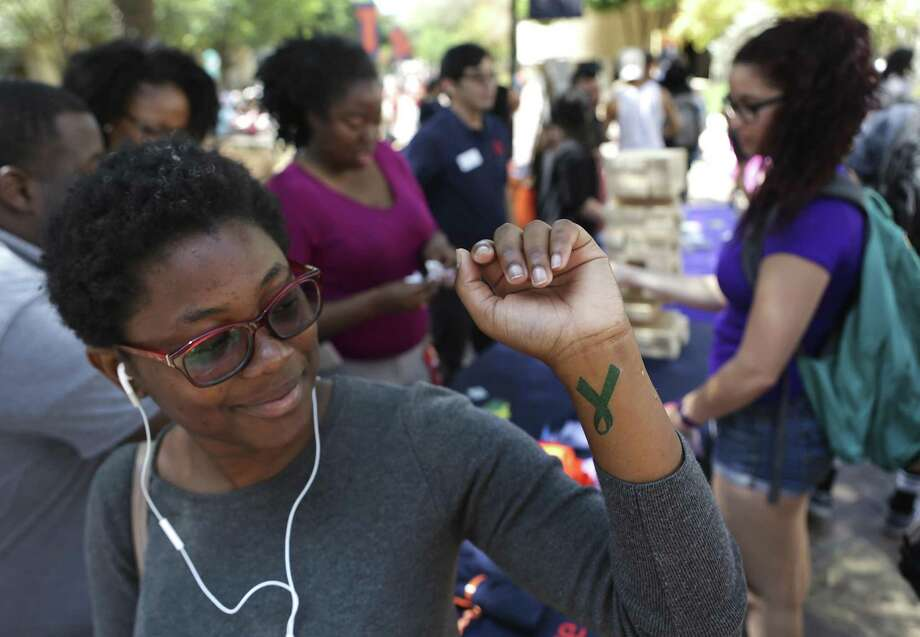 Hillary Ndongo, a freshman UTSA studnet from Cameroon, looks at her new temporary tatoo she received at the Campus Residents Halls booth during ACtion Day raising awareness of sexual assaults at UTSA on Tuesday, April 4, 2017. The teal colored ribbon is a sign for sexual assault awarness. Photo: Bob Owen, Staff / San Antonio Express-News / ©2017 San Antonio Express-News