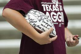A Texas A&M fan holds an autographed football during the Texas A&M spring football game at Kyle Field on Saturday, April 8, 2017, in College Station. ( Brett Coomer / Houston Chronicle )