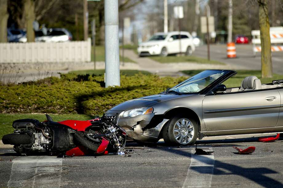 Midland police investigate the scene of a motorized scooter and car accident at the intersection of Bay City Road and Waldo Avenue on Saturday in Midland. Bay City Road at Waldo Avenue remained closed during the investigation. Photo: NICK KING | Nking@mdn.net