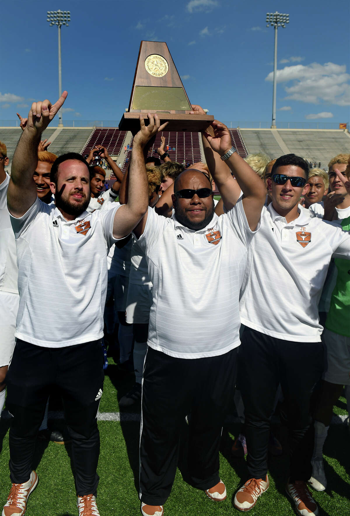 Dobie Head Boys Soccer Coach Justo Manrique, center, flanked by Assistant Coaches Jose Esparza, left, and Nicolas Condon, right, hoists the Region III-6A Boys Championship trophy won by the Longhorns in a shootout over the Channelview Falcons in their finals matchup at Abshier Stadium in Deer Park on Saturday, April 8, 2017. (Photo by Jerry Baker/Freelance)