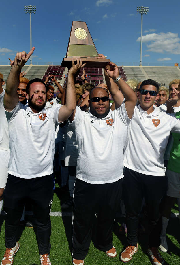 Dobie Head Boys Soccer Coach Justo Manrique, center, flanked by Assistant Coaches Jose Esparza, left, and Nicolas Condon, right, hoists the Region III-6A Boys Championship trophy won by the Longhorns in a shootout over the Channelview Falcons in their finals matchup at Abshier Stadium in Deer Park on Saturday, April 8, 2017. (Photo by Jerry Baker/Freelance) Photo: Jerry Baker/For The Chronicle