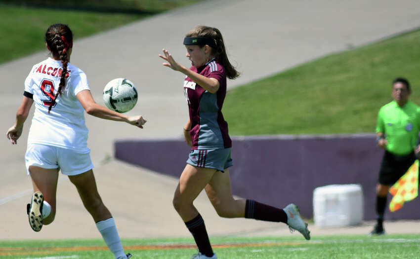 Cinco Ranch junior midfielder Katie Becker, right, pushes the ball downfield against Tompkins senior midfielder JoAnnie Ramos (9) during the 1st half of their Girls Region III-6A Soccer Final at Abshier Stadium in Deer Park on Saturday, April 8, 2017. (Photo by Jerry Baker/Freelance)
