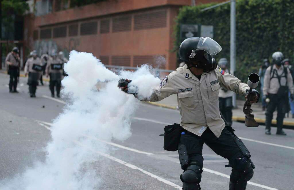 A Bolivarian National Police officer throws a tear gas bomb toward demonstrators during a protest in Caracas, Venezuela, Saturday. Photo: Fernando LLano, STF / Copyright 2017 The Associated Press. All rights reserved.
