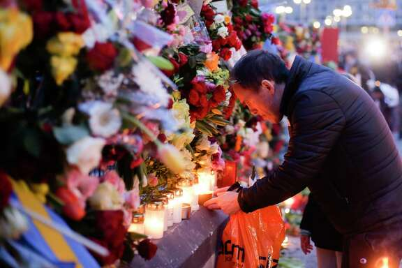 """A man lights a candle at a fence near the department store, Ahlens, Saturday, April 8, 2017, following Friday's suspected terror attack in central Stockholm, Sweden. Swedish prosecutor Hans Ihrman said a person has been formally identified as a suspect """"of terrorist offences by murder"""" after a hijacked truck was driven into a crowd of pedestrians and crashed into a department store on Friday. (AP Photo/Markus Schreiber)"""