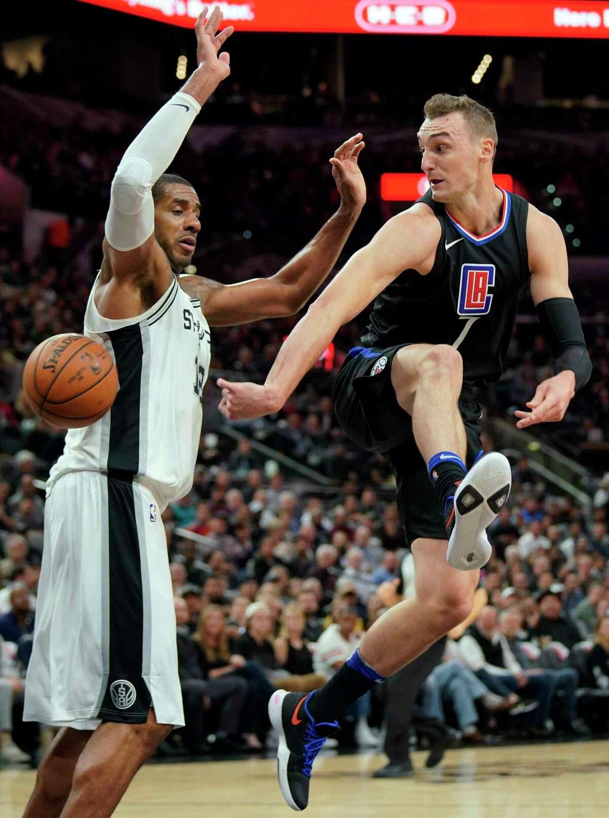 Los Angeles Clippers forward Sam Dekker, right, passes around San Antonio Spurs forward LaMarcus Aldridge during the first half of an NBA basketball game, Monday, Dec. 18, 2017, in San Antonio. (AP Photo/Darren Abate)