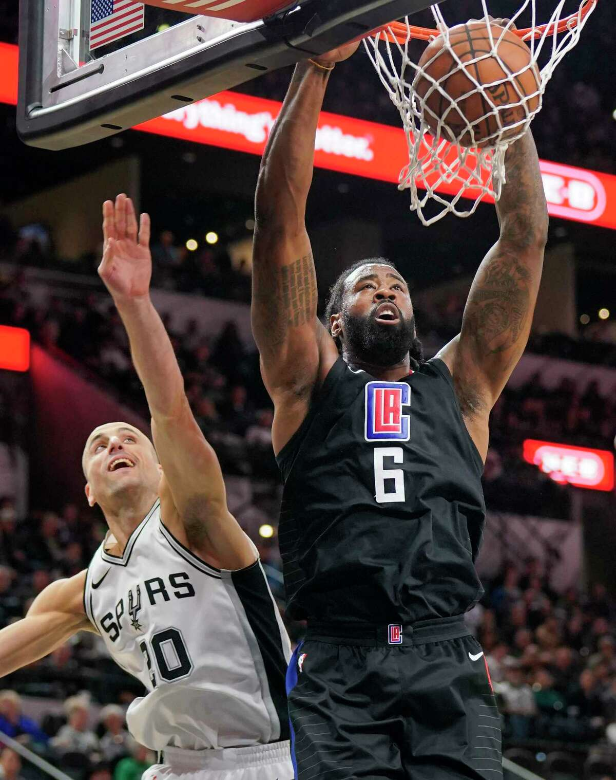 Los Angeles Clippers center DeAndre Jordan (6) dunks as San Antonio Spurs guard Manu Ginobili looks on during the first half of an NBA basketball game, Monday, Dec. 18, 2017, in San Antonio. (AP Photo/Darren Abate)