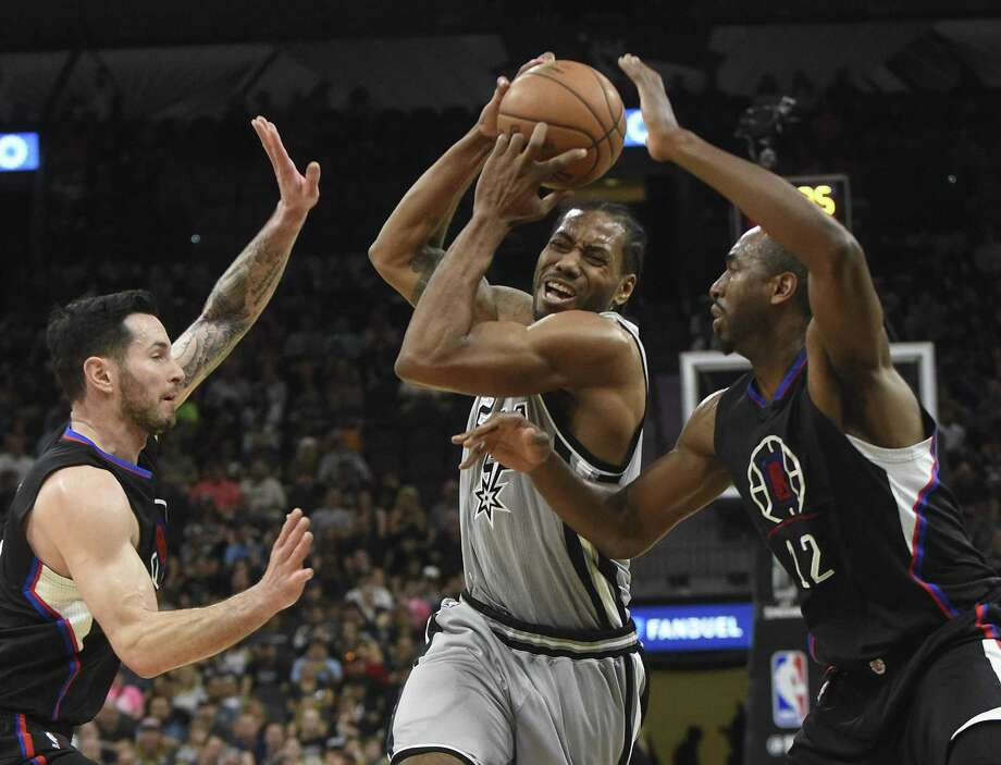 Kawhi Leonard of the SanAntonio Spurs, middle, drives toward the basket as J.J. Redick, left, and Luc Mbah a Moute (12) of the Los Angeles Clippers defend during first-half NBA action at the AT&T Center on April 8, 2017. Photo: Billy Calzada / San Antonio Express-News / San Antonio Express-News
