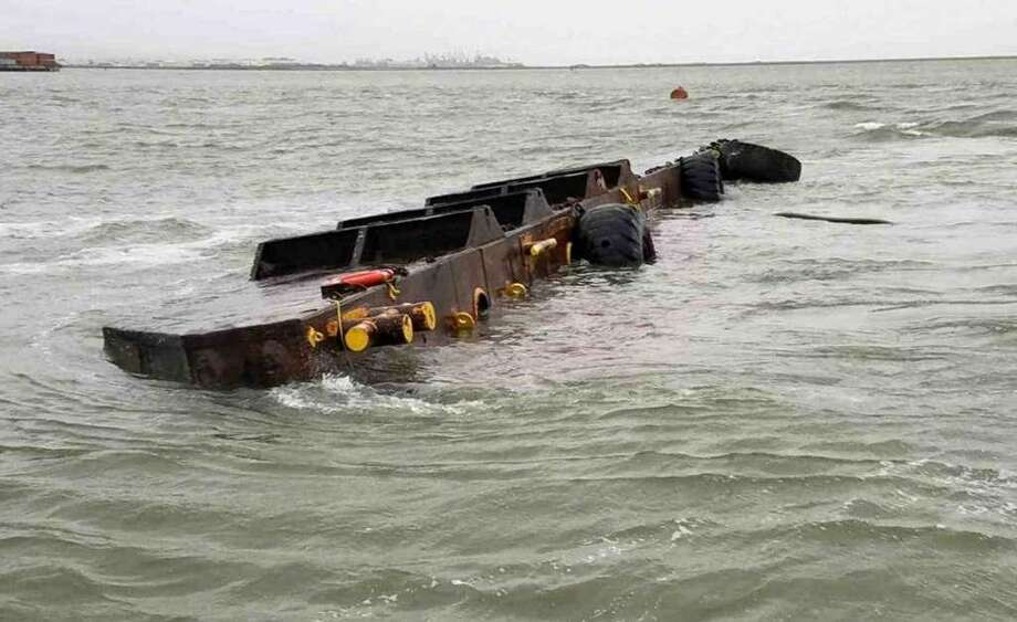 This photo provided by the U.S. Coast Guard shows the 112-foot freight barge Vengeance after capsizing near Yerba Buena Island Friday. Crews Sunday were working to contain a fuel spill.