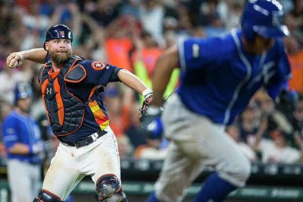 Houston Astros catcher Brian McCann (16) throws out Kansas City Royals second baseman Raul Mondesi on a bunt attempt during the seventh inning of a major league baseball game at Minute Maid Park on Sunday, April 9, 2017, in Houston.