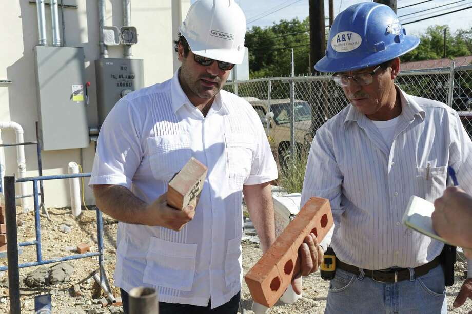 Local developer Kevin Covey, left, checks out a D'Hanis brick that he picked out himself at the company's factory for a retail center he's building in Southtown. His construction manager, Adrian Perez, is at right. Photo: JERRY LARA /San Antonio Express-News / © 2017 San Antonio Express-News