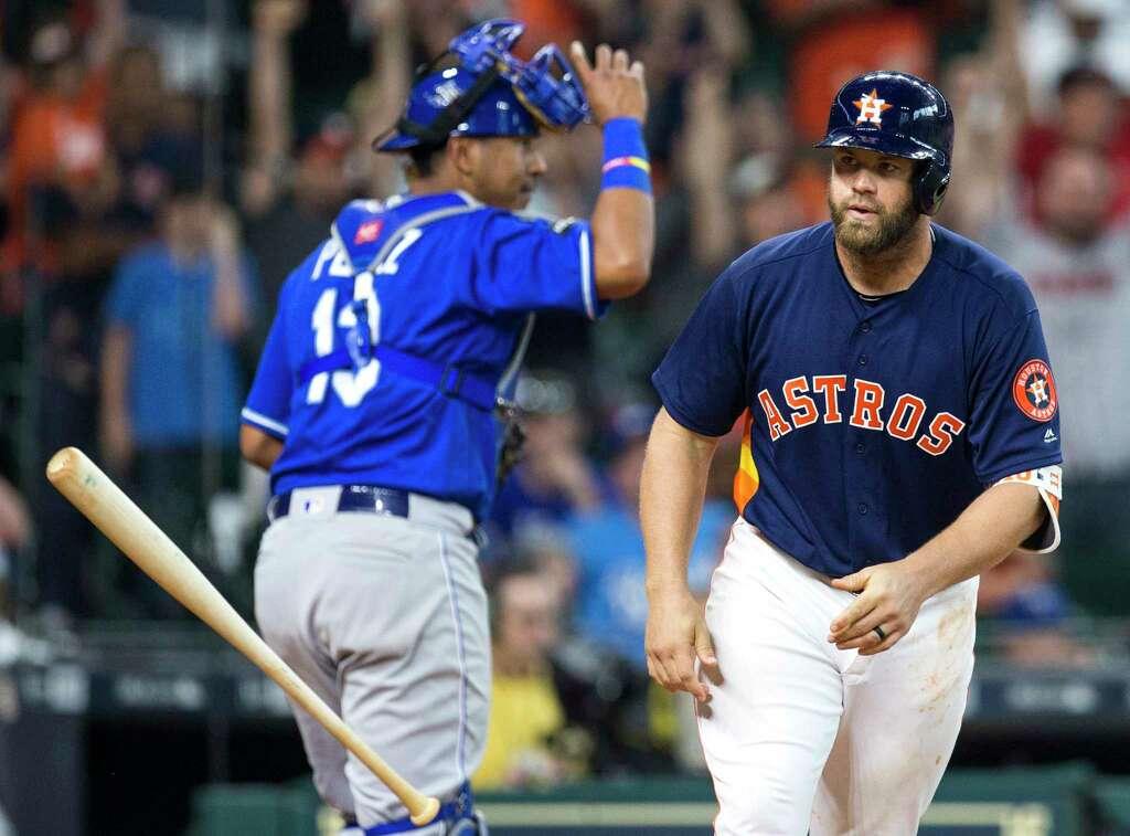 Houston Astros catcher Evan Gattis (11) tosses his bat toward the dugout as he
