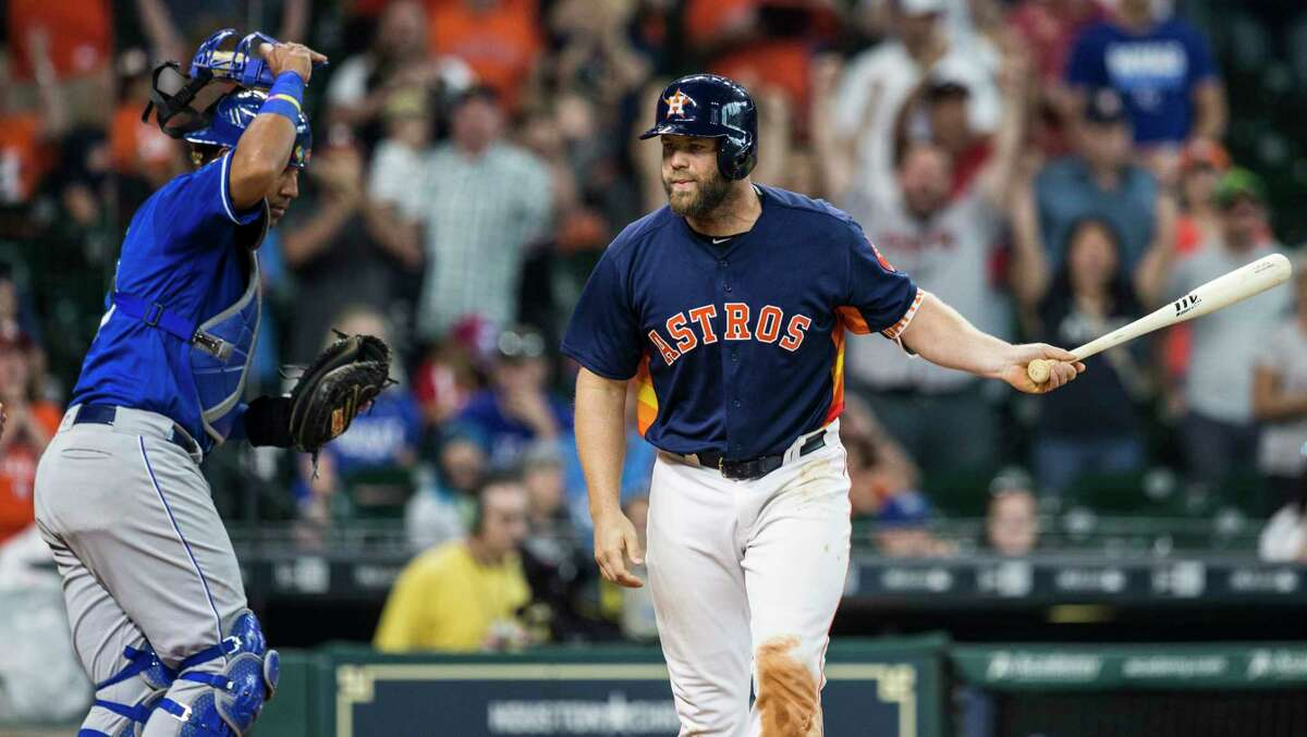 Houston Astros catcher Evan Gattis (11) tosses his bat toward the dugout as he draws a bases-loaded walk during the 12th inning to give the Astros a 5-4 win over the Kansas City Royals at Minute Maid Park on Sunday, April 9, 2017, in Houston.