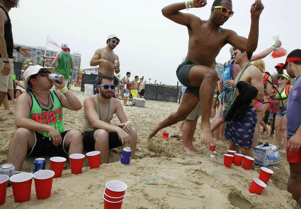 Ross House jumps over a beer pong game while celebrating spring break on the beach Thursday, March 17, 2016, at South Padre Island, Texas. (Nathan Lambrecht/The Monitor via AP) MAGS OUT; TV OUT; MANDATORY CREDIT
