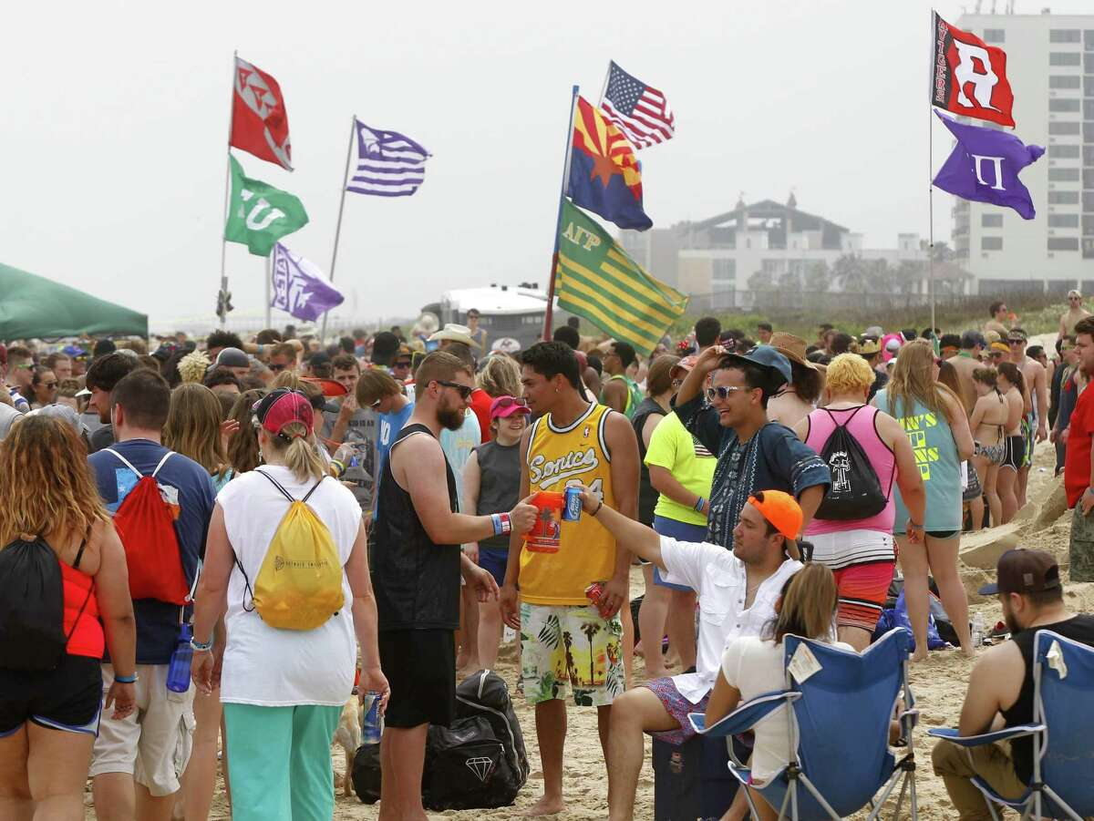 Spring breakers sit on the beach under flags from their universities Thursday, March 17, 2016, at South Padre Island, Texas. (Nathan Lambrecht/The Monitor via AP) MAGS OUT; TV OUT; MANDATORY CREDIT