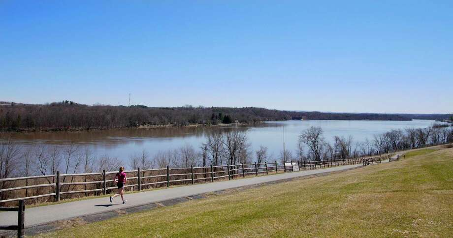 A runner makes her way along a bike path with the Mohawk River in the background on Sunday, April 9, 2017, in Niskayuna, N.Y.    (Paul Buckowski / Times Union)