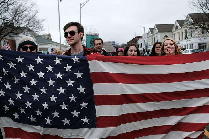 WESTPORT, CT - MARCH 26: People march to protest against the policies and presidency of Donald Trump on March 26, 2017 in Westport, Connecticut. Over 2,000 people marched through the small and wealthy Connecticut town with many carrying flags and signs critical of Trump. The event was organized by the Westport Democratic Town Committee and DefenDemocracy, a grassroots organization founded by Westport women.  (Photo by Spencer Platt/Getty Images)