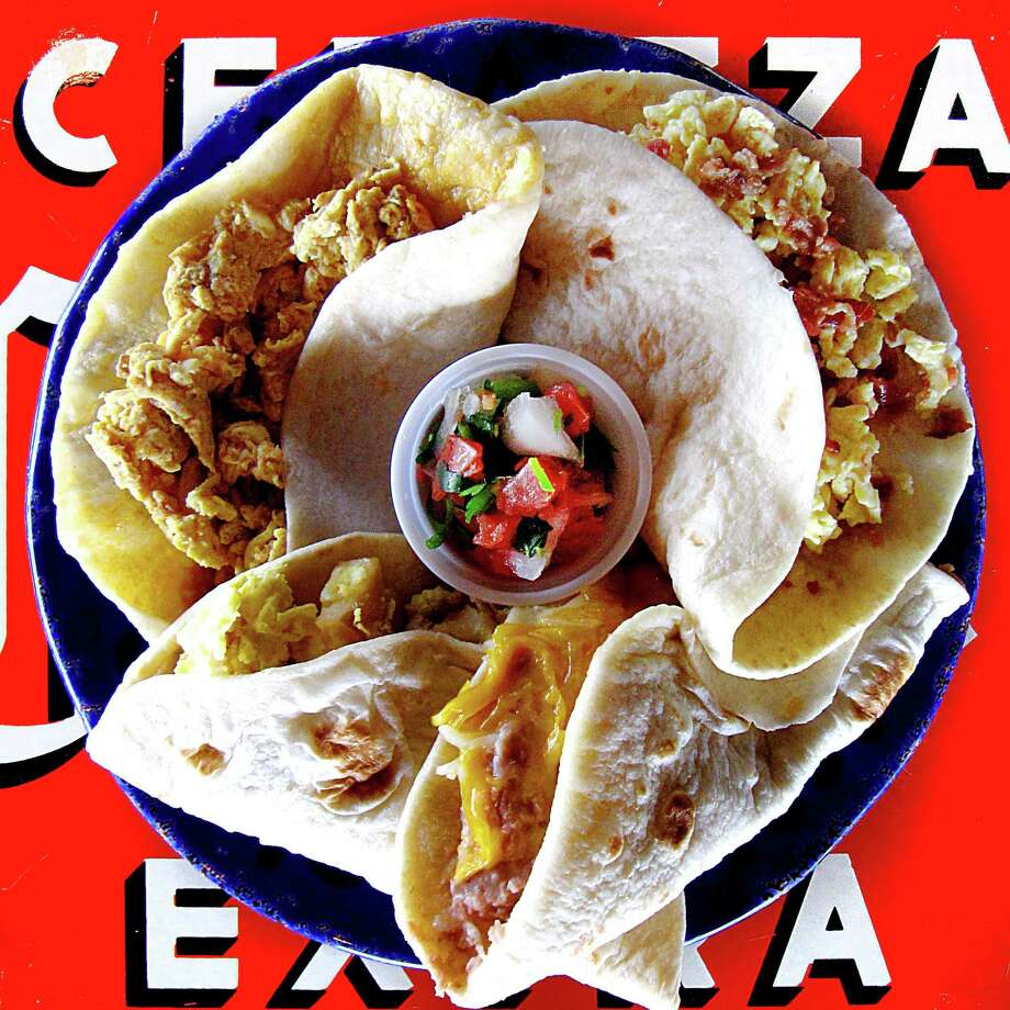 Breakfast tacos from the original Taco Cabana on San Pedro Avenue. Clockwise from top left: chorizo and egg, bacon and egg, bean and cheese and potato and egg. Photo: Mike Sutter /San Antonio Express-News