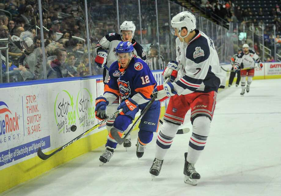 Josh Holmstrom, left, of the Sound Tigers and Adam Tambellini of the Wolf Pack battle for a loose puck during Sunday's game at Webster Bank Arena in Bridgeport. Photo: Gregory Vasil / For Hearst Connecticut Media / Connecticut Post Freelance