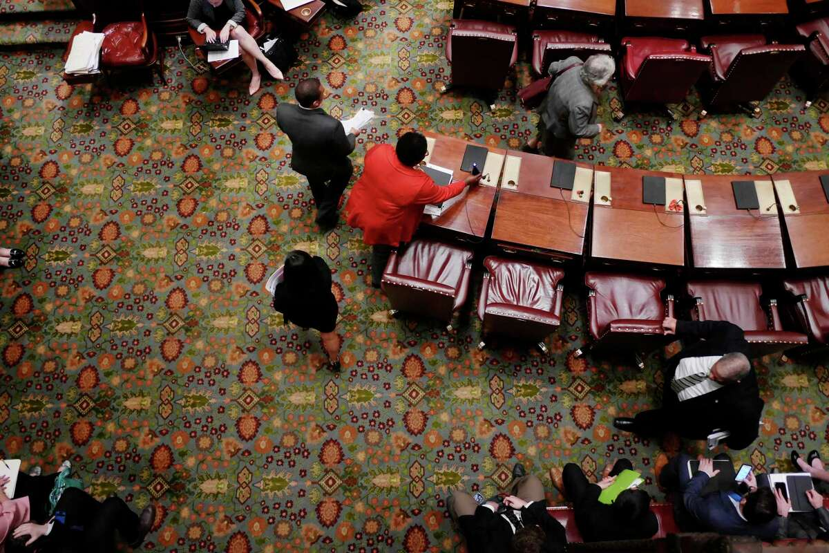 Senators make their way to their desks before the start of the session at the Capitol on Sunday, April 9, 2017, in Albany, N.Y. (Paul Buckowski / Times Union)