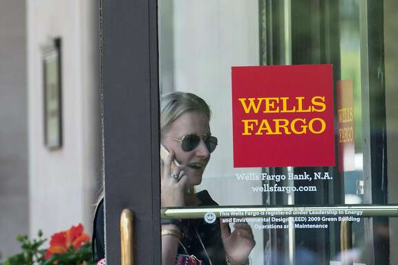 "(FILES) This file photo taken on May 27, 2016 shows a woman walking into a Wells Fargo bank in Washington, DC. Wells Fargo took back another $75 million in pay from two former executives who played key roles in the bank's fake accounts scandal, the bank announced on April 10, 2017. The US banking giant said it demanded or ""clawed back"" an additional $28 million from former chief executive John Stumpf, who led the bank at the time of the scandal, and $47 million more from former community banking chief Carrie Tolstedt, whose division was at the heart of the problem.  / AFP PHOTO / Nicholas KammNICHOLAS KAMM/AFP/Getty Images"