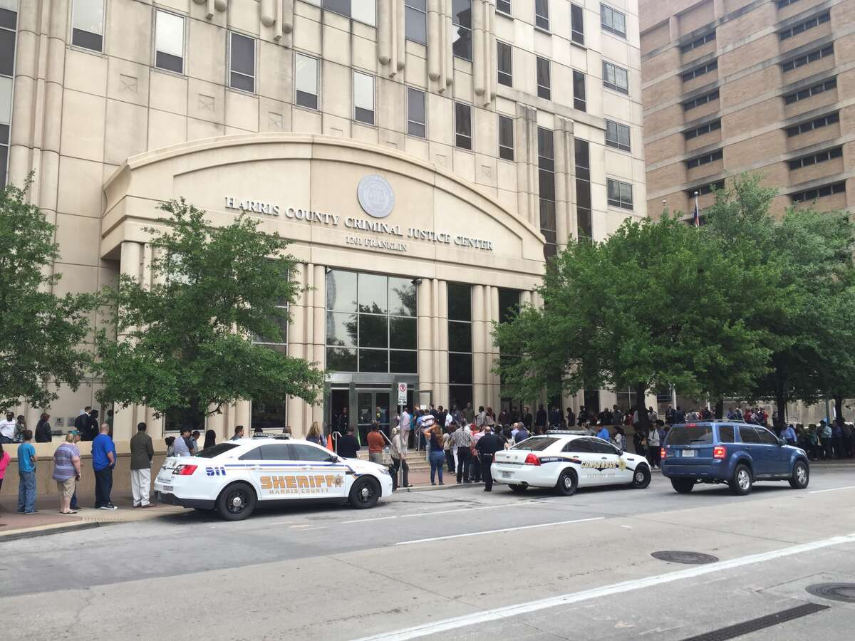 Lines of people wound around the Harris County criminal courthouse in downtown Houston after an apparent false fire alarm triggered a response from the Houston Fire Department. (Brian Rogers / Houston Chronicle)