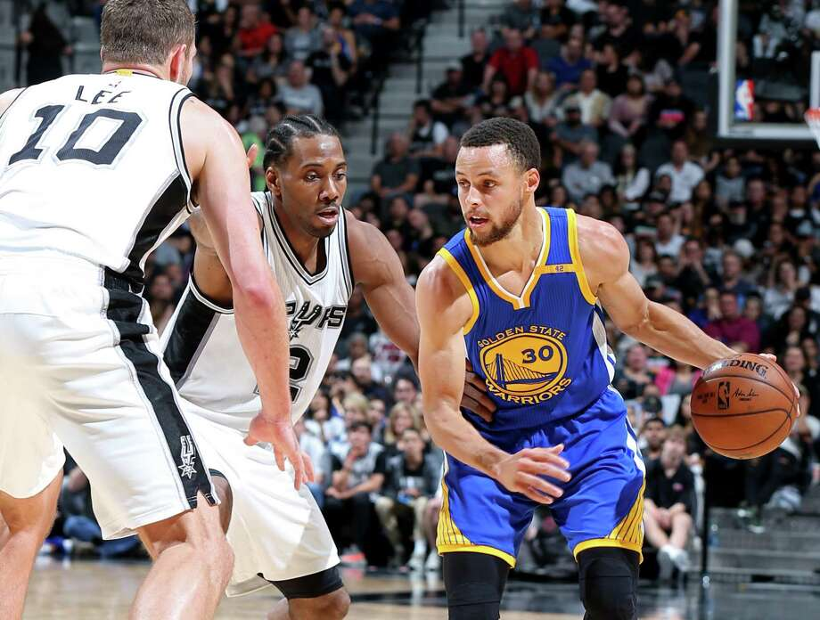 The top-seeded Warriors' Stephen Curry looks for room around  David Lee and Kawhi Leonard of the Spurs, the No. 2 seed, on March 29 at the AT&T Center. Photo: Edward A. Ornelas / San Antonio Express-News / © 2017 San Antonio Express-News
