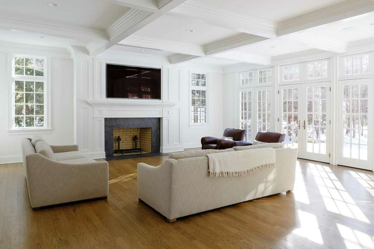 The family room has a fireplace with a yellow brick firebox, a coffered ceiling, and French doors to the bluestone patio and backyard.