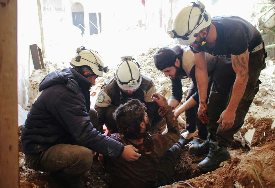 Members of the Syrian civil defense   remove a man from   rubble  following a  strike by government forces on a rebel-held area. Photo: Mohamad Abazeed / Getty Images / AFP or licensors