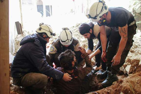 Members of the Syrian civil defense   remove a man from   rubble  following a  strike by government forces on a rebel-held area.