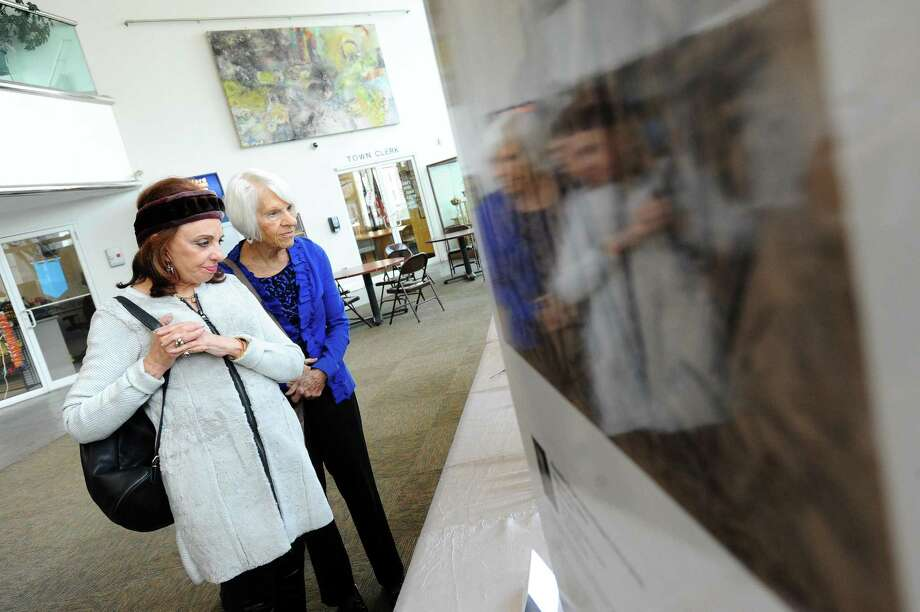 Stamford Carol Brewer, left, and Norwalk resident Suzanne Horn read the description on one of the paintings on display as part of the Holocaust Memorial Exhibit inside the Government Center in downtown Stamford on Monday. Photo: Michael Cummo / Hearst Connecticut Media / Stamford Advocate
