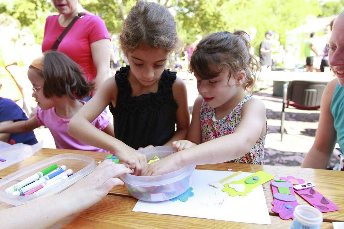 In this file photo, Sophie Seaver and Ella Seaver use their arts and crafting skills to create bookmarks during a Family Fun Day at the Jewish Community Center of Stamford. The JCC is offering temporary space to the Italian Center after a fire caused damage to its preschool and locker room facilities.