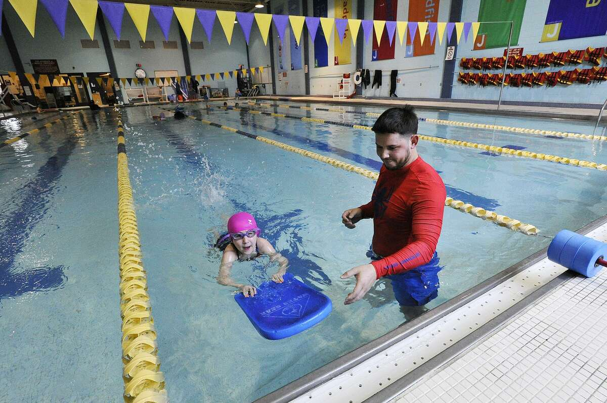 In this file photo, Daniel Servelli gives a swim lesson to Elle Riker at the Jewish Community Center in Stamford. The JCC is offering temporary space to the Italian Center after a fire caused damage to its preschool and locker room facilities.