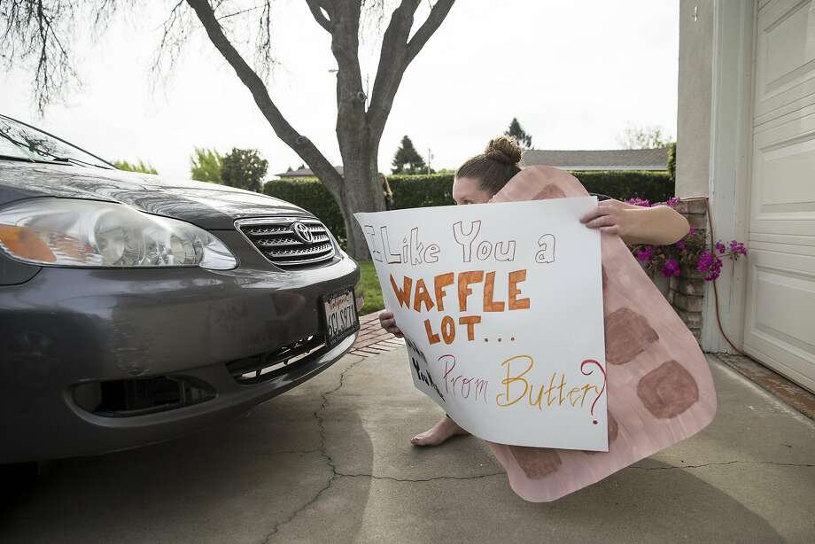 "Promposals are often elaborate, but sometimes sweet and heartfelt, proposals to attend prom. Rachel Knoop hides behind a car in her driveway while waiting to surprise her boyfriend with a ""promposal"" in Sunnyvale on April 5, 2017. Knoop asked her boyfriend Tim Goode to prom dressed as a waffle, which is his favorite food. Photo: Laura Morton, Special To The Chronicle"