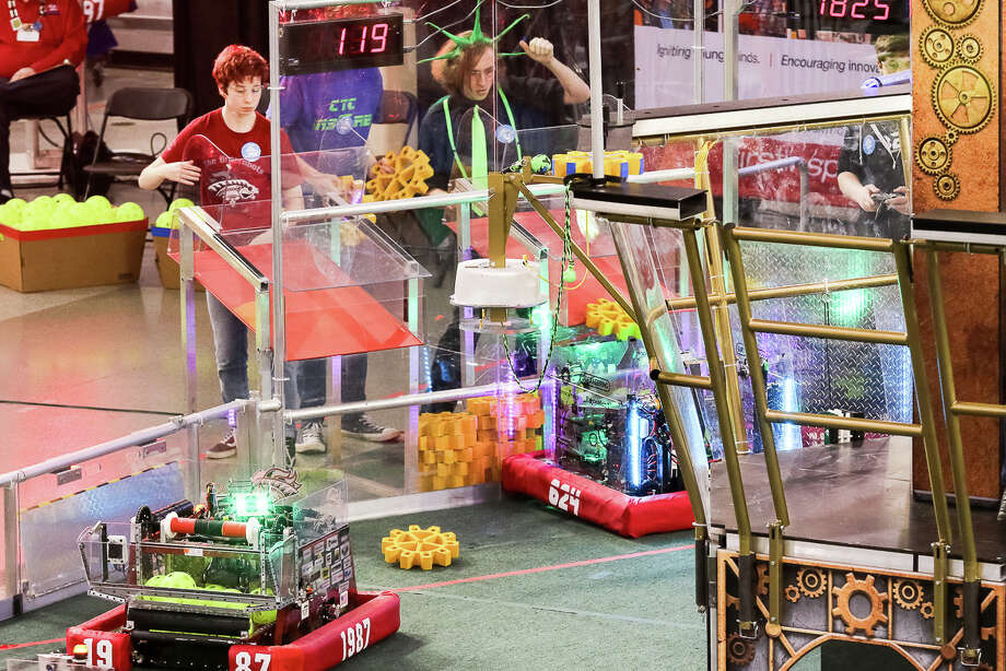 During a playoff match, CRyptonite human player, Greg Tarnowski drops a gear into the chute at the alliance's loading station. The CRyptonite robot will deliver the gear across the field where it will be collected and used to turn rotors to score points. To his right, their alliance partner human player gets ready to do the same as his team's robot approaches the chute. Photo: Cinco Ranch High