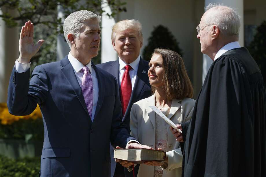 Supreme Court Justice Anthony Kennedy (right) administers the judicial oath to Neil Gorsuch (left), accompanied by his wife, Marie Louise, as President Trump watches at the White House. Photo: Evan Vucci, Associated Press