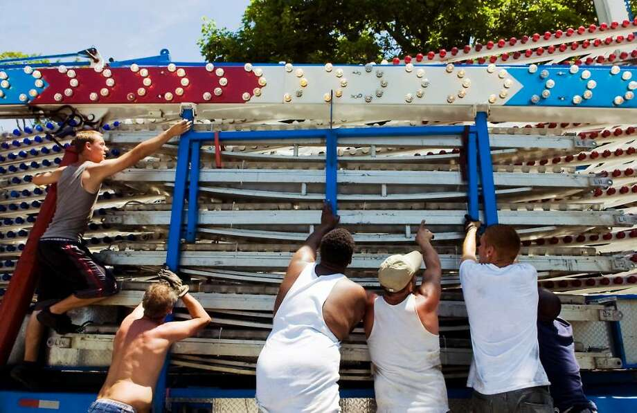 "Carnival workers with Dreamland Amusements set up ""The Wheel"" ride for the Grecian Festival at Annunciation Church in Stamford, Conn. on Wednesday June 2, 2010.  The festival runs June 3 - June 6. Photo: Kathleen O'Rourke / Stamford Advocate"