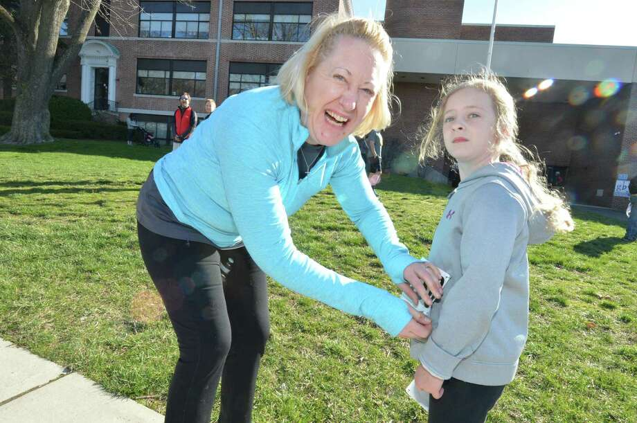 Seven-year-old Heather Conlon and mom Julianne from Shelton get their badges pinned on before they start The Donnelly Dash April 9 at Tomlinson Middle School in Fairfield. Photo: Alex Von Kleydorff / Hearst Connecticut Media / Norwalk Hour